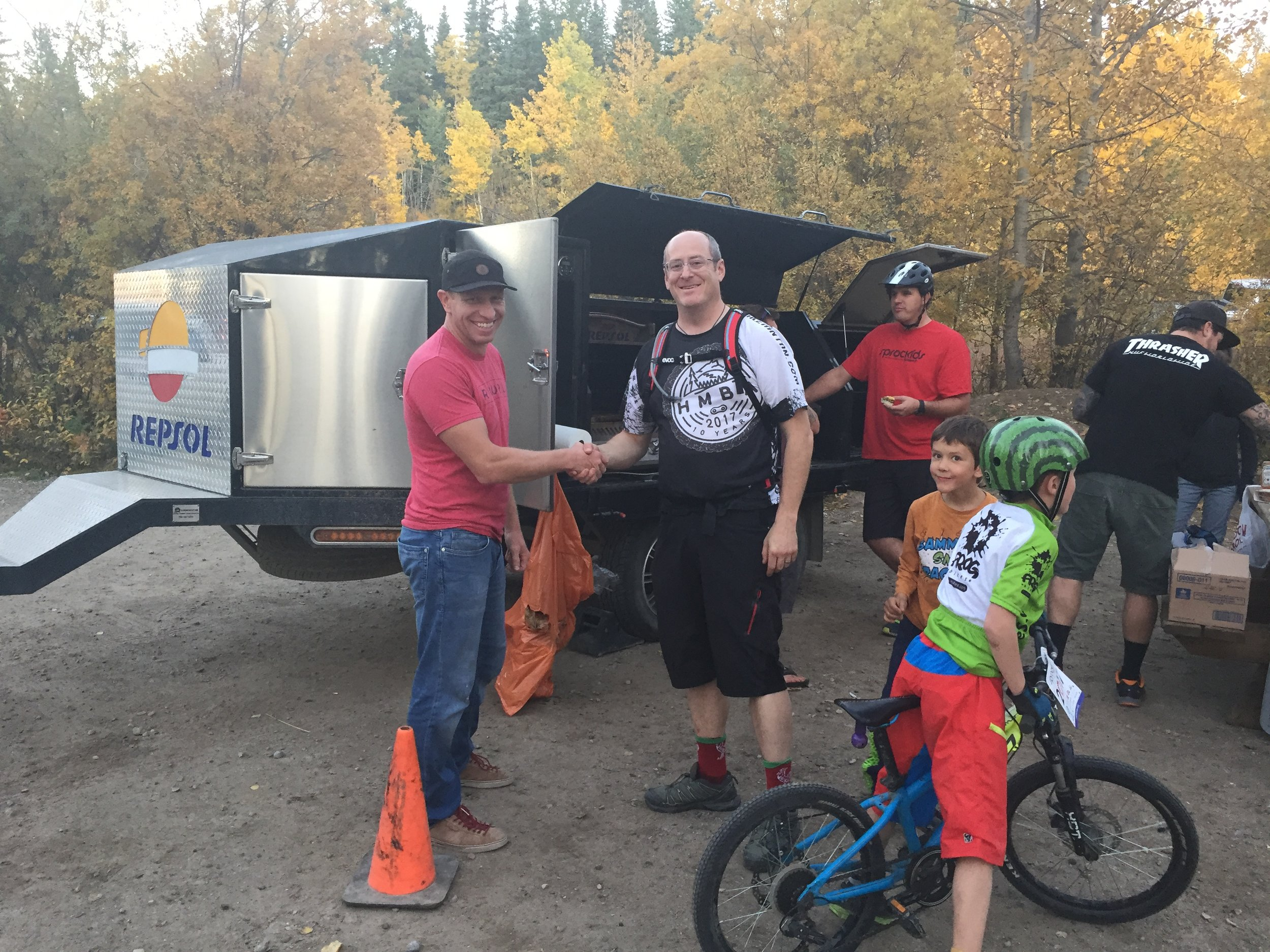 Tim Trahan, Hinton Sprockids Coordinator, thanks Jesse Kirillo, representative of REPSOL, for donating the use of their mobile BBQ for the program's year-end session.