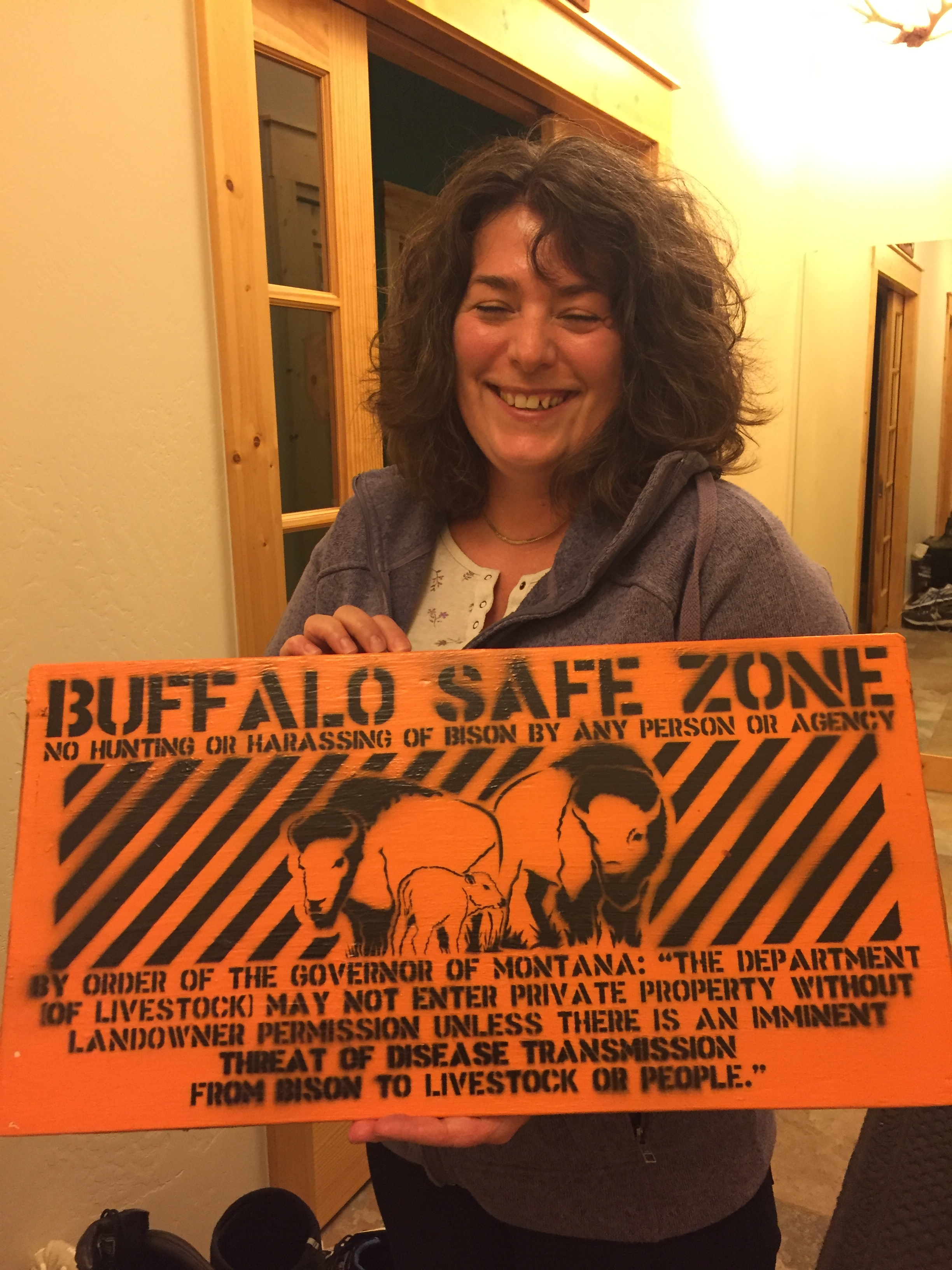 Sabina Strauss holds up a sign meant to inform state officials that they do not want bison hazed off of their property.