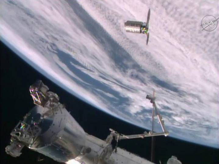 Richard and Nancy's artwork, along with the student's experiments, arriving at the ISS. The Cygnus spacecraft is about to be pulled in by the robotic arm.