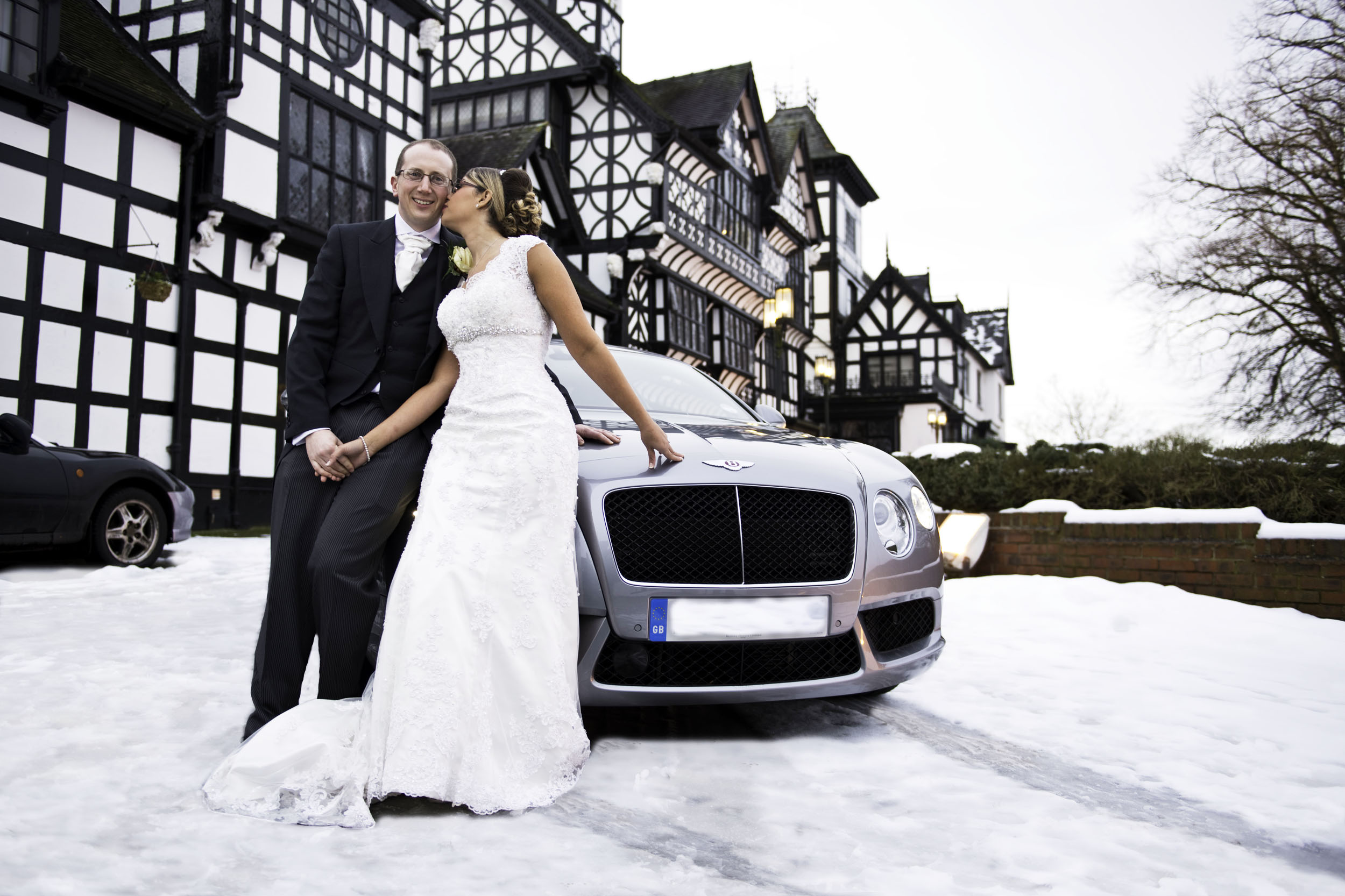 The Wild Boar Inn black and white building with snow all around - stunning background for this lovely couple