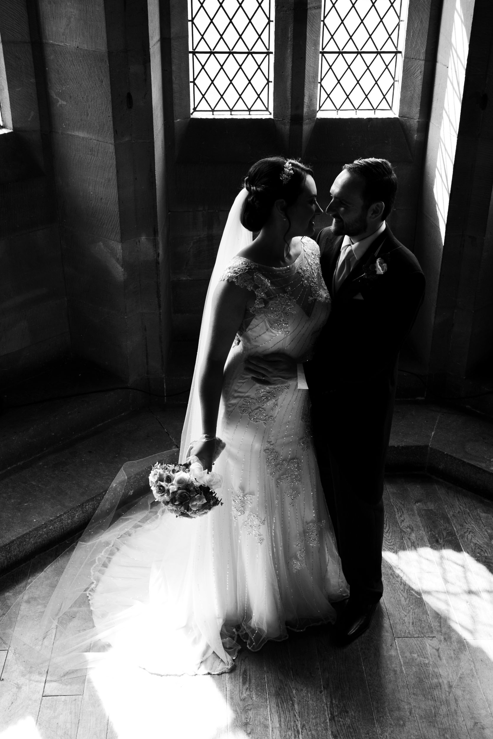 In partial silhouette this high contrast image maintains the intimacy of the couple's first few hours together as newlyweds - taken at  Peckforton Castle  in the bay window