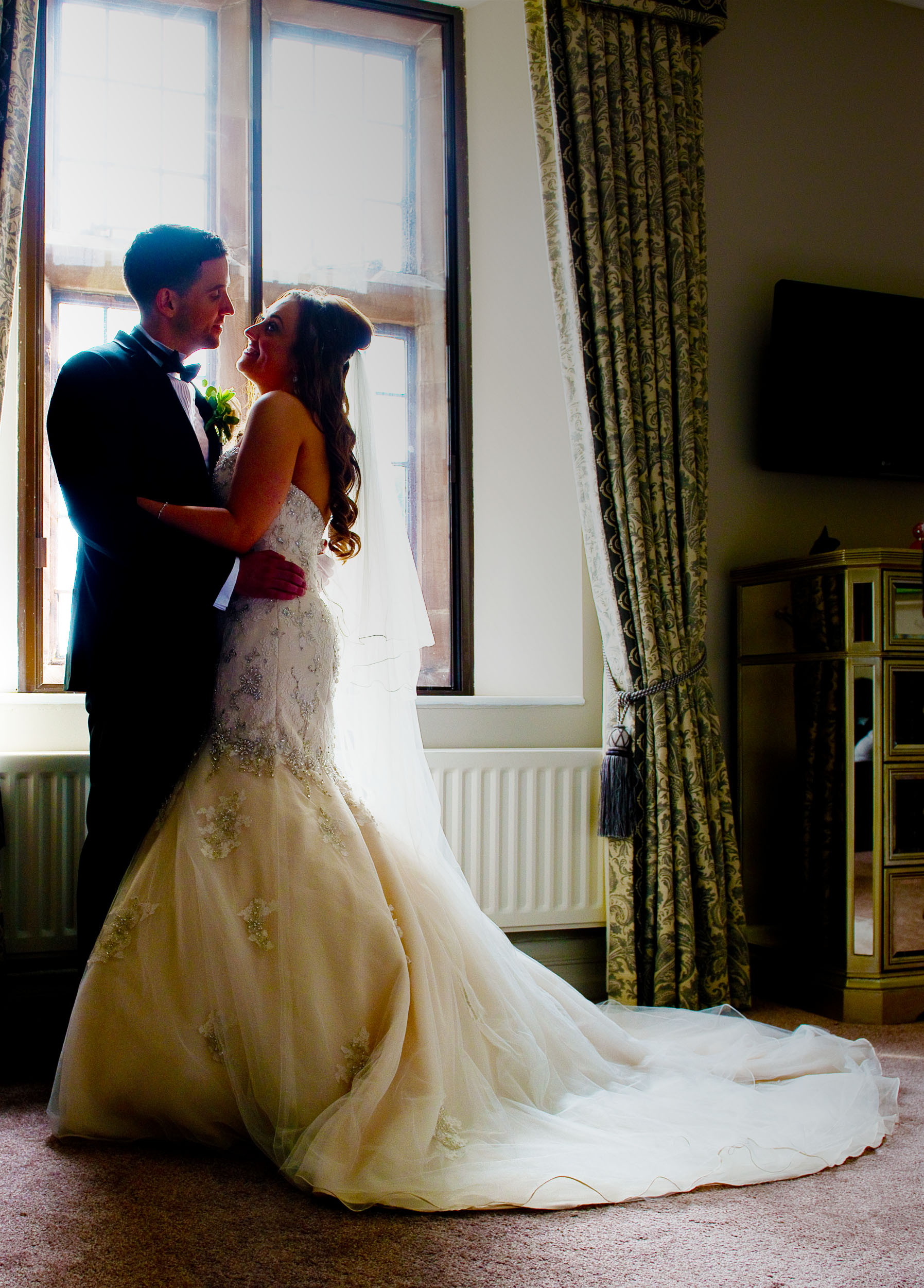 Spotlit in the window, this couple only have eyes for each other at their  Wrenbury Hall  wedding
