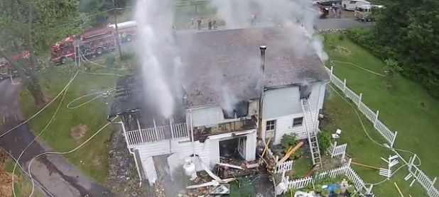 Screenshot of firefighters firing high-pressure hoses at the drone.