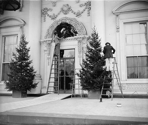 Workmen putting up Christmas decorations on the front of the White House, December 19, 1939. Photo by Harris & Ewing.