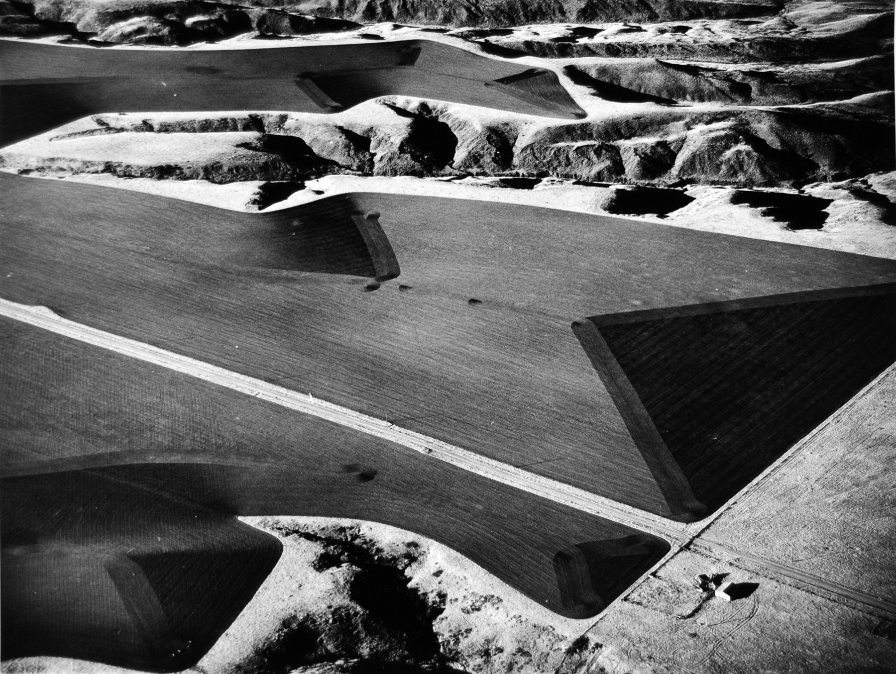 """Marilyn Bridges (American, b. 1948), Farmer's Edge, South Dakota, 1984; 2011:314  In 1976, upon seeing the Nazca Indian """"runway"""" lines in Peru, Marilyn Bridges decided to become a pilot. Bridges is credentialed to fly single- and multi-engine land and sea aircraft, and she even owns her own Cessna, but she does not pilot when she photographs. Waiting for just the right light, she directs the pilot where to fly and when to tilt in angles ranging from low oblique to vertical to get the right picture. The process is technically demanding both in terms of flying--the plane must slow down to just a notch above stalling even at a shutter speed of 1/1000th of a second--and in terms of photographing. Unable to slow the plane any more than she does, Bridges extends the speed of her Tri-X film by pushing it (a development technique). So that her landscapes resonate as land and not as abstractions, she shoots from an altitude no greater than 1000 feet above the earth, and she prefers to get as close as 200 feet. She usually shoots with a 6×7 Pentax medium-format camera, sometimes a Leica 35mm, and always from an open window."""