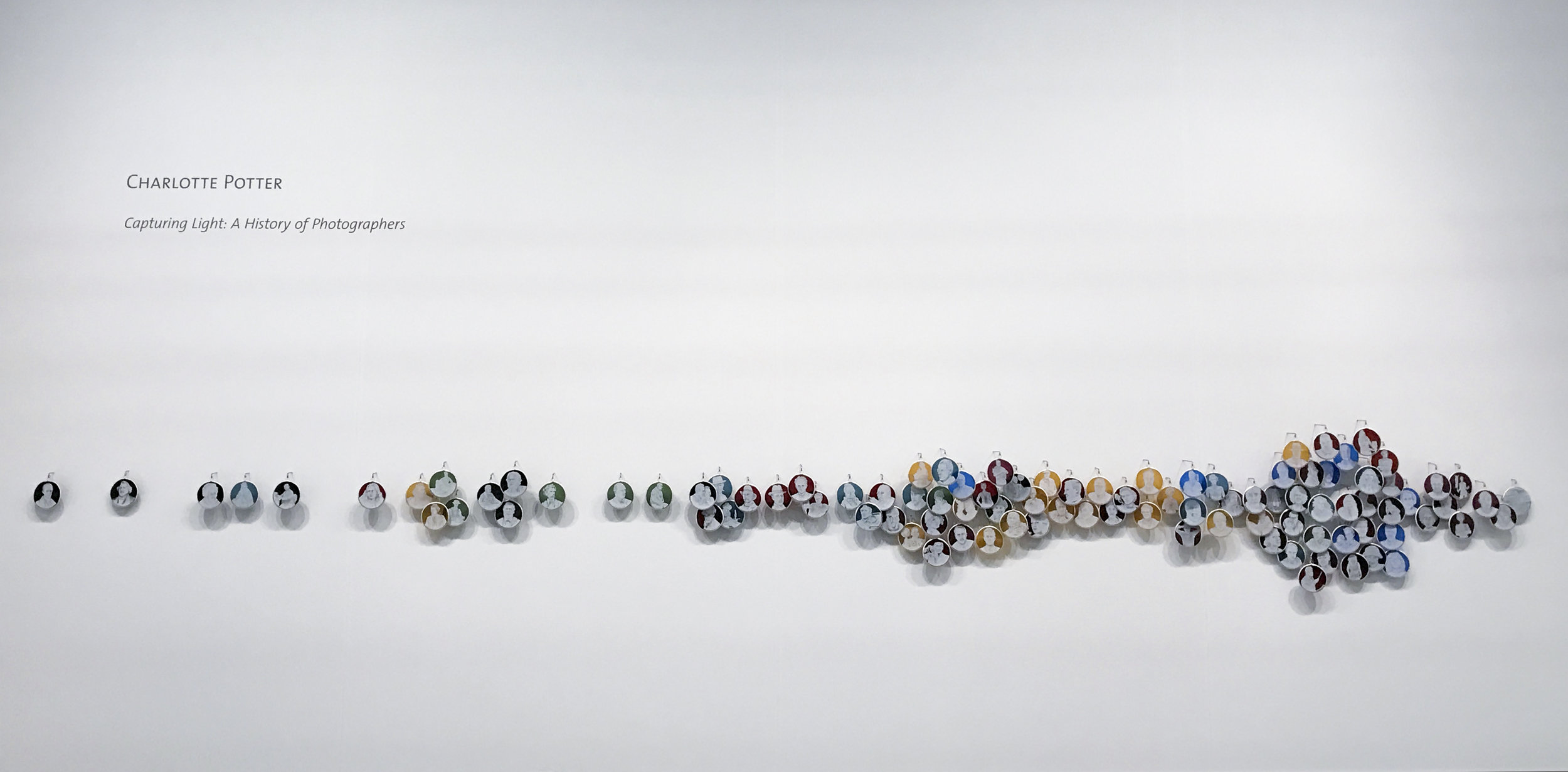 Capturing Light: A History of Photographers , Charlotte Potter, 2017, Hand engraved glass, silver, tin, stainless steel, 3 x 3 inches each cameo, 13 feet long installation. On view at Booth 503.