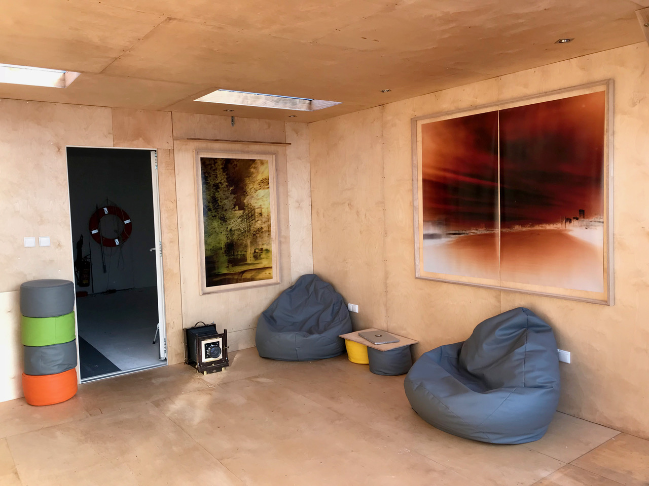Artist living studio space on the floating camera with photographs from the project hanging on the walls.