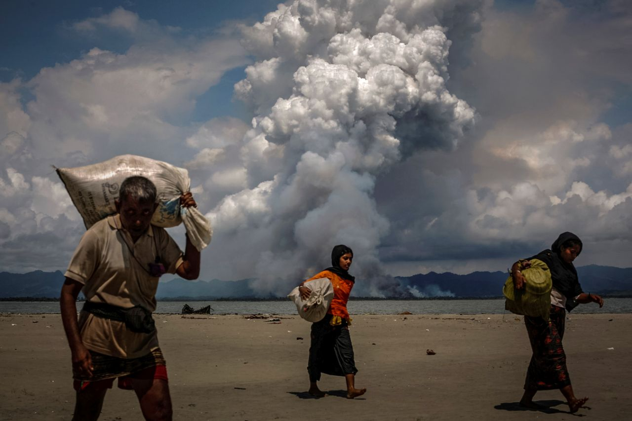 Smoke is seen on the Myanmar border as Rohingya refugees walk on the shore after crossing the Bangladesh-Myanmar border by boat through the Bay of Bengal, in Shah Porir Dwip, Bangladesh, Sept.11, 2017. (Photo: Danish Siddiqui/Reuters)