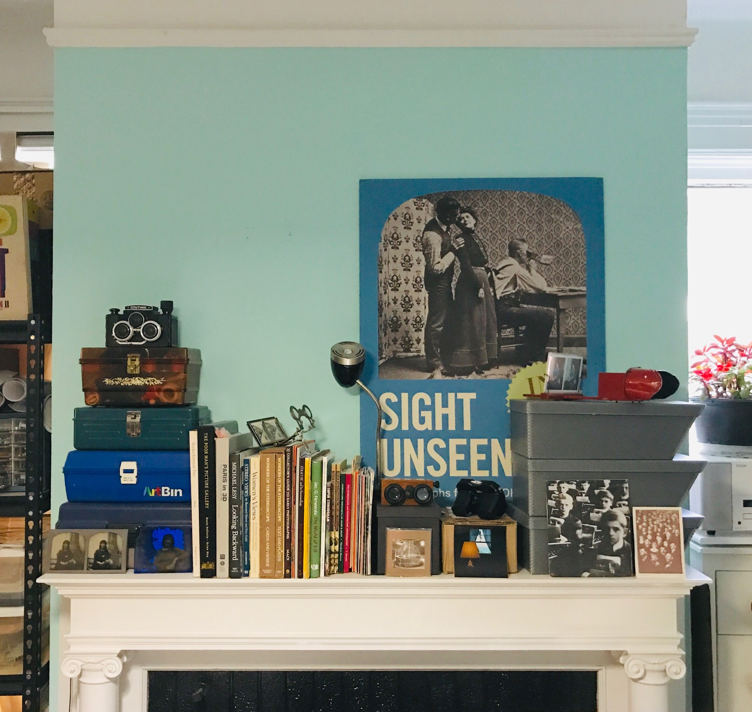 Colleen Woolpert 's studio bookshelf featuring a poster for her 2012 exhibition on the history of stereographs.