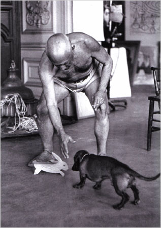 """Lump the dachshund, in the South of France in 1957, with Picasso and a presumably undervalued gift: a Picasso rabbit, suitable for chewing.CreditDavid Douglas Duncan/From """"Picasso and Lump: A Dachshund's Odyssey"""" (Bulfinch Press)"""