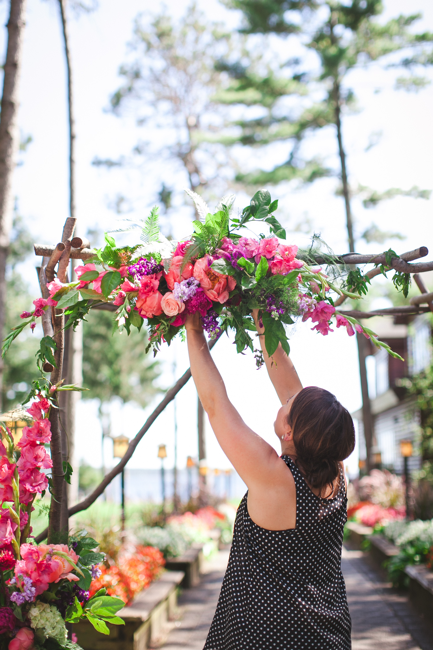 Kate Kuepers of  Bloom Designs  floralizing a wedding ceremony arbor at  Grand View Lodge  in Nisswa, Minnesota