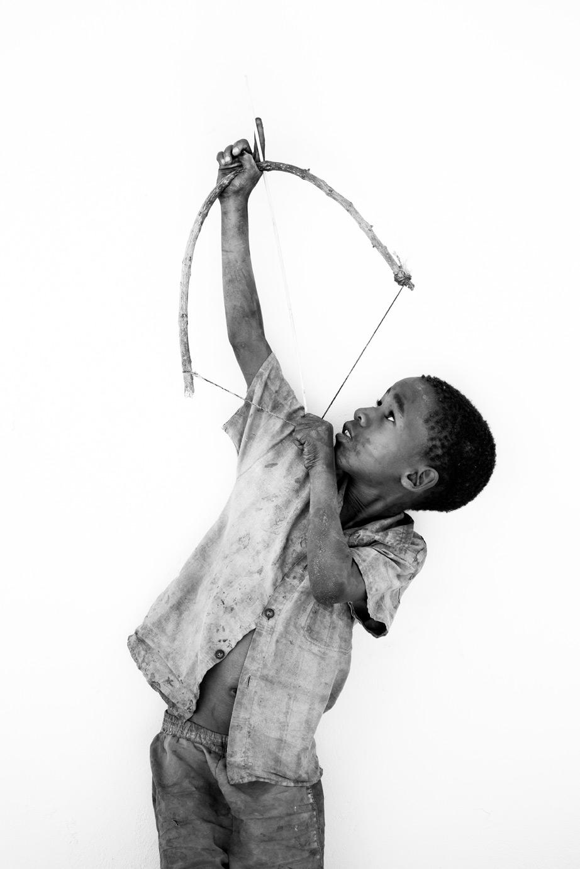 China shoots his handmade bow and arrow up at the sky in Botswana