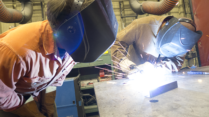 As a previous professor of sculpture at San Jose State University Carrington helped students learn about welding and metal works, pictured on the left, he watches a student practice a tight weld at the Foundry Metal Works in San Jose, CA.  Photo © Aimee Santos