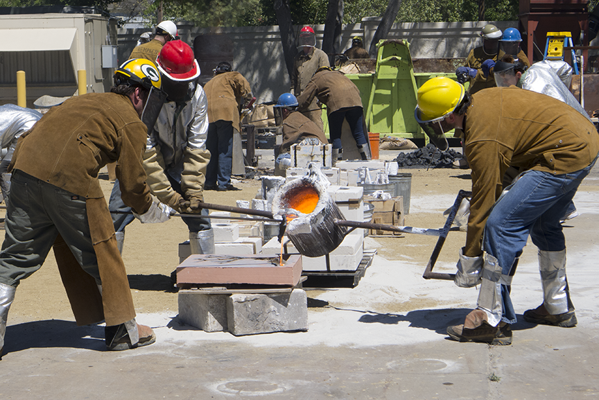 Carrington, on the left, manages the flow of iron during a past iron pour at the San Jose State University Metal Works Foundry.  Photo © Aimee Santos