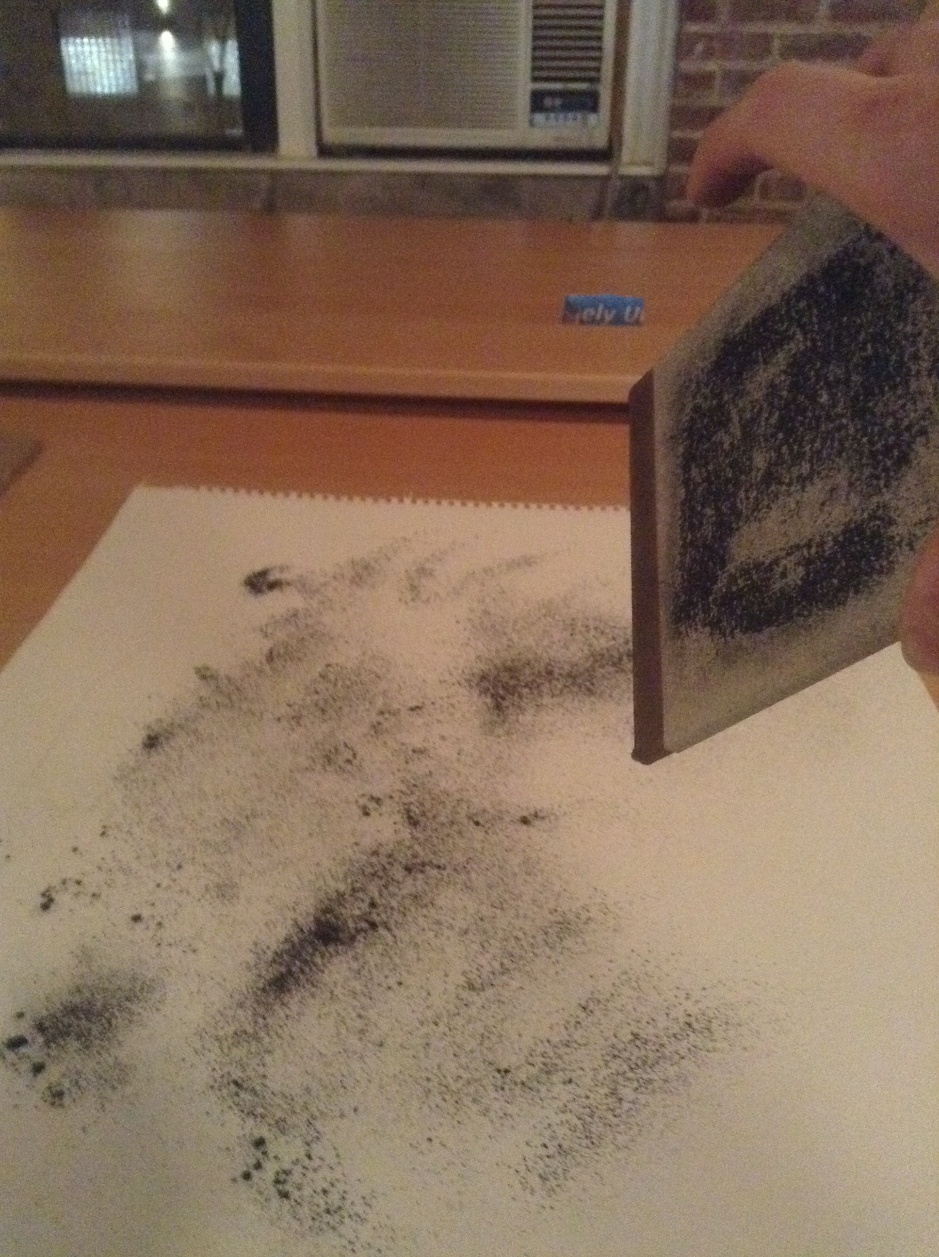 Shaking the graphite powder onto the back of the drawing.