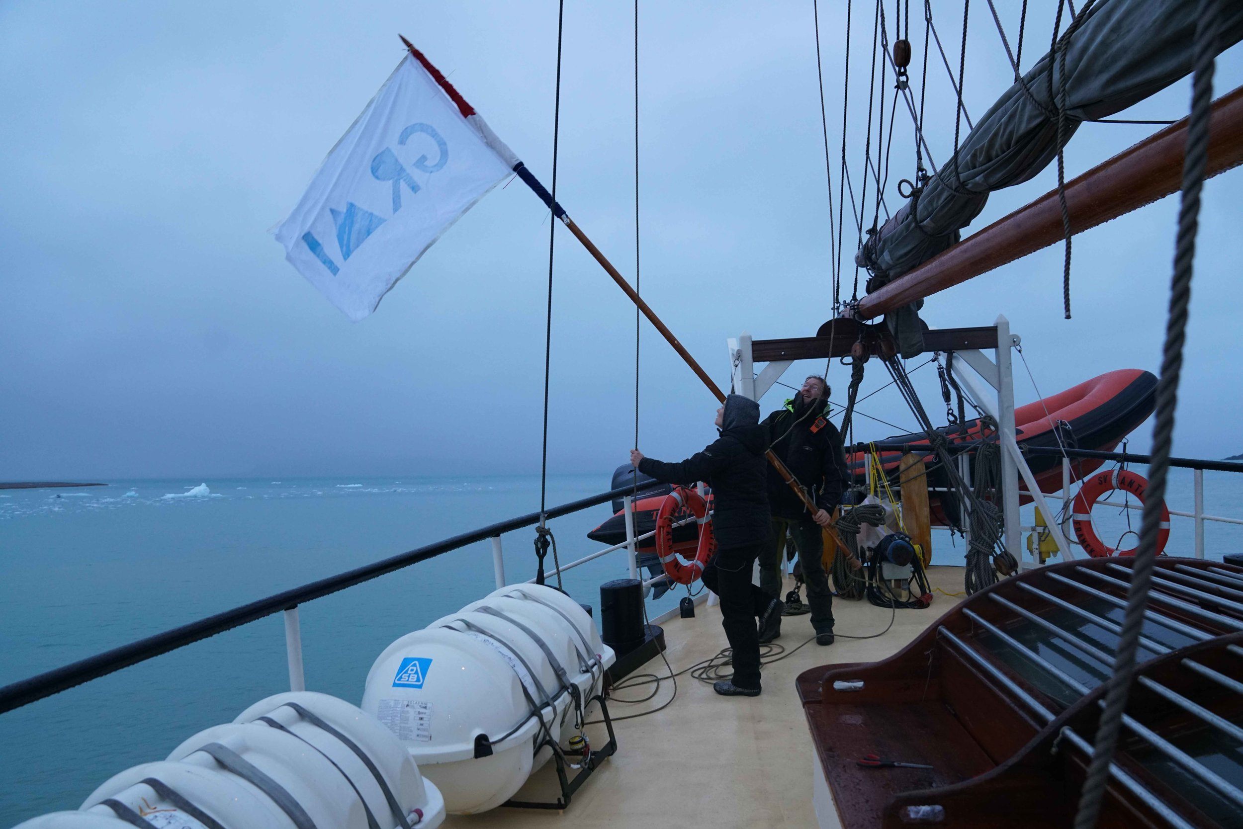 Hoisting the GRMI flag at Fjortende Julibukta. Photo credit courtesy of the artist.