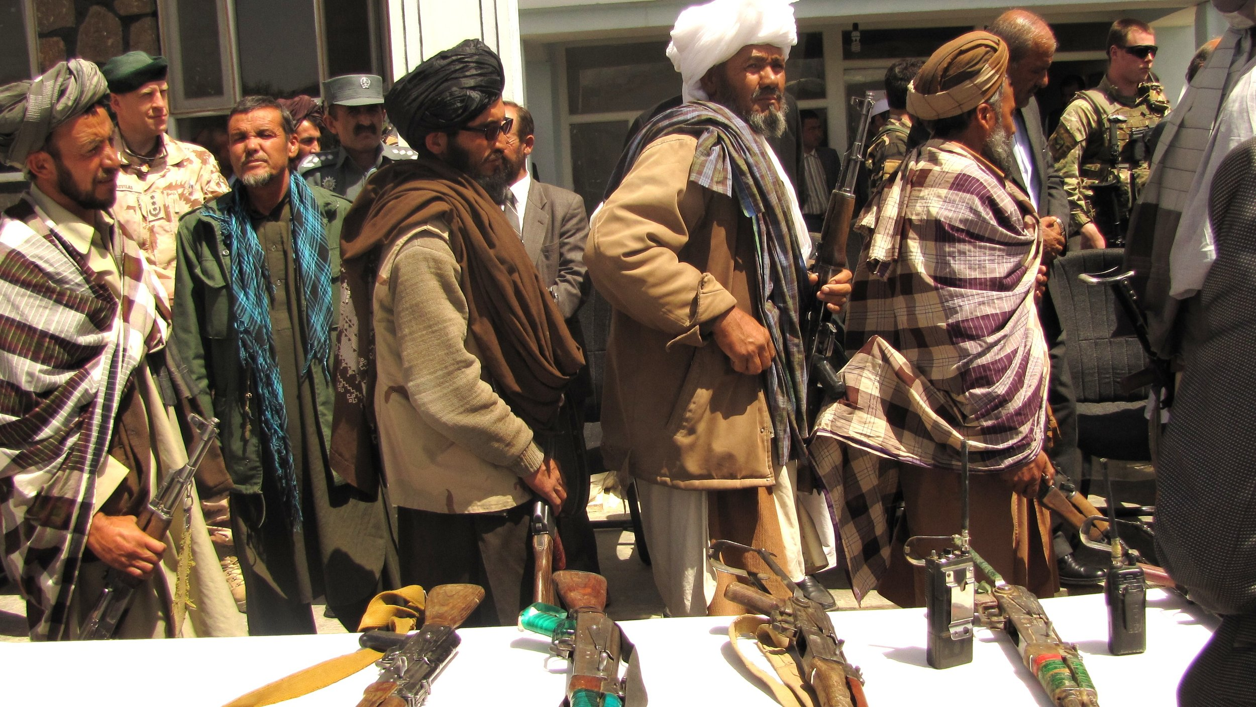 Former Taliban fighters line up to handover their Rifles to the Government of the Islamic Republic of Afghanistan during a reintegration ceremony at the provincial governor's compound.