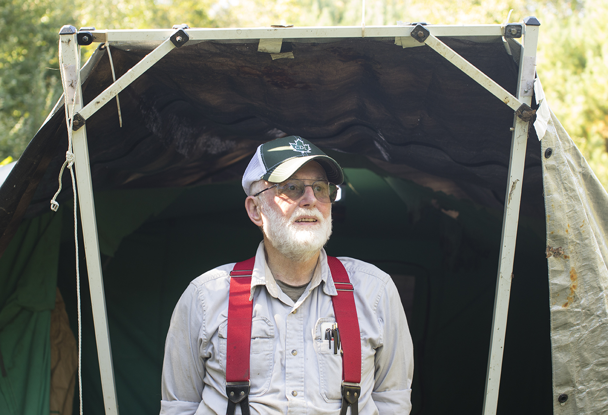 George is seen at his bee yard in Chaplin, Connecticut, standing in front of a makeshift shed made out of tarps and a metal frame. The shed contains his beekeeping equipment and other necessities for taking care of the bees.(Jackson Mitchell)