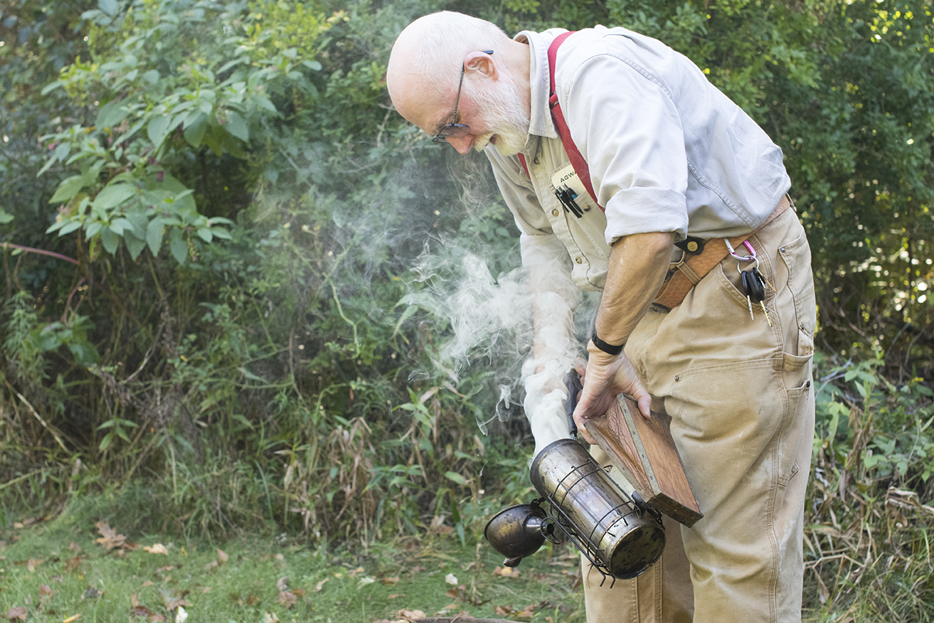 George is seen igniting his smoker before putting on his beekeeping equipment at his bee yard in Chaplin, Connecticut, just off Route 6. (Jackson Mitchell)