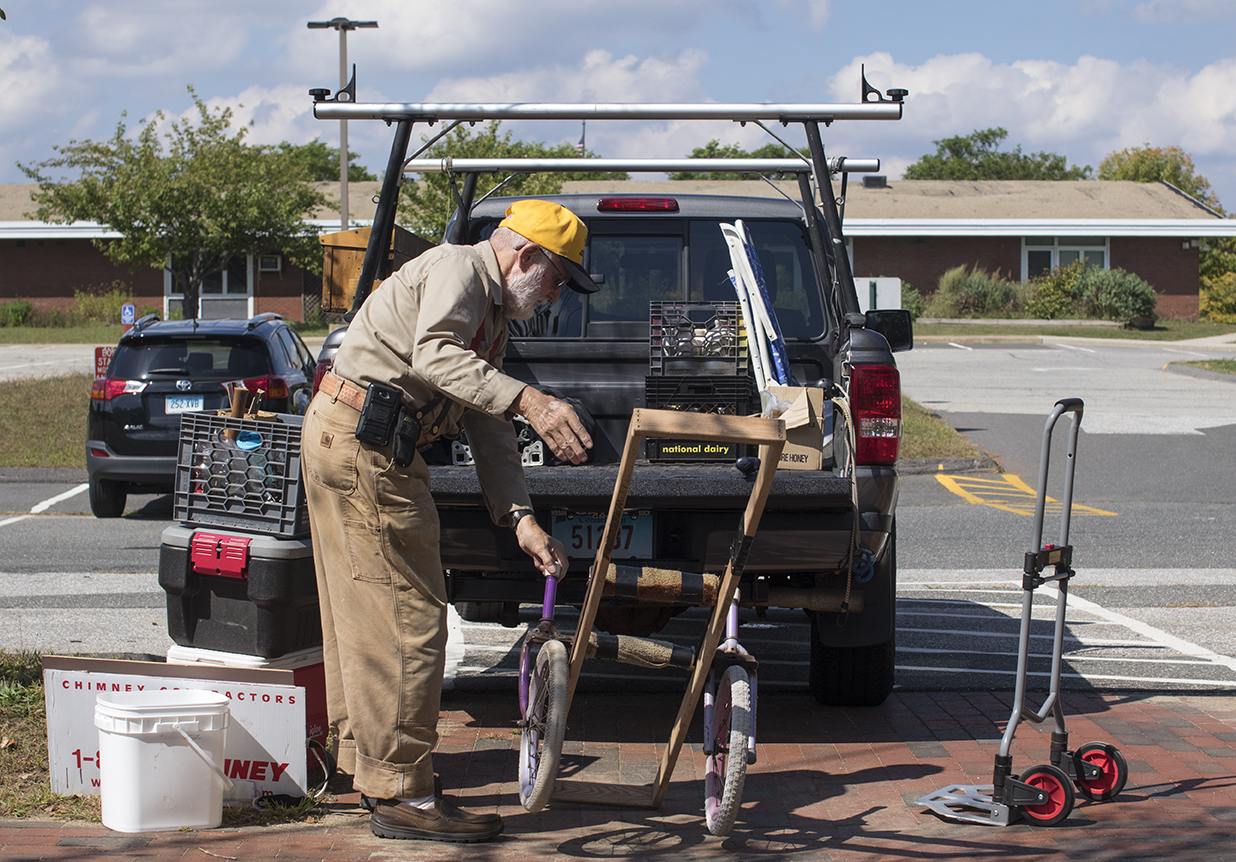 George unloads equipment from the back of his truck prior to setting up his tent at the Storrs Farmers Market on Saturday, Sept. 19, 2015. George made the cart he is seen unloading out of wooden planks and two old bicycle tires. (Jackson Mitchell)