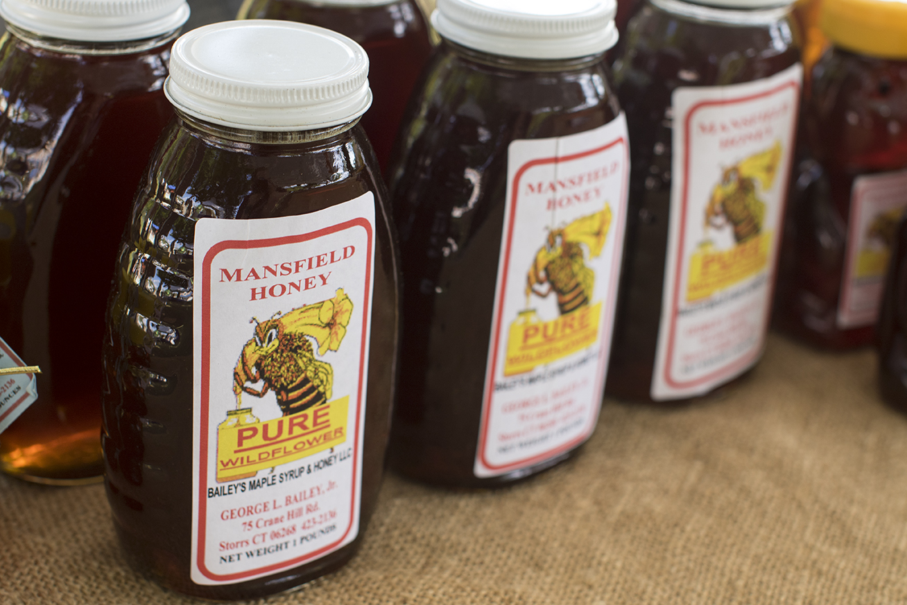 George's Mansfield Honey bottles are seen on a table inside his tent at the Storrs Farmers Market on Saturday, Sept. 19, 2015. (Jackson Mitchell)