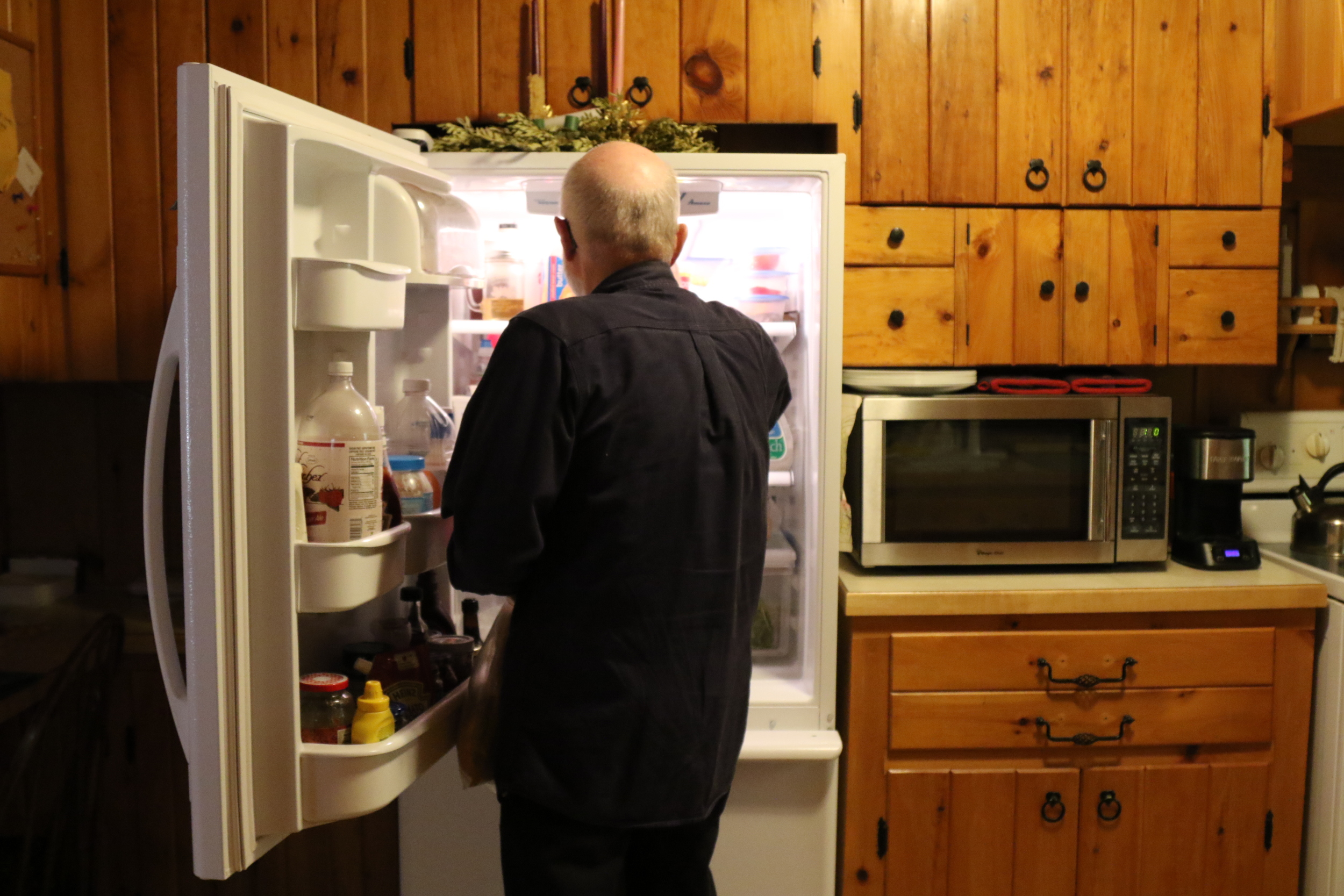 George is seen getting food out of the refrigerator in his home in Mansfield, Connecticut before making lunch for Ann. (Jackson Mitchell)