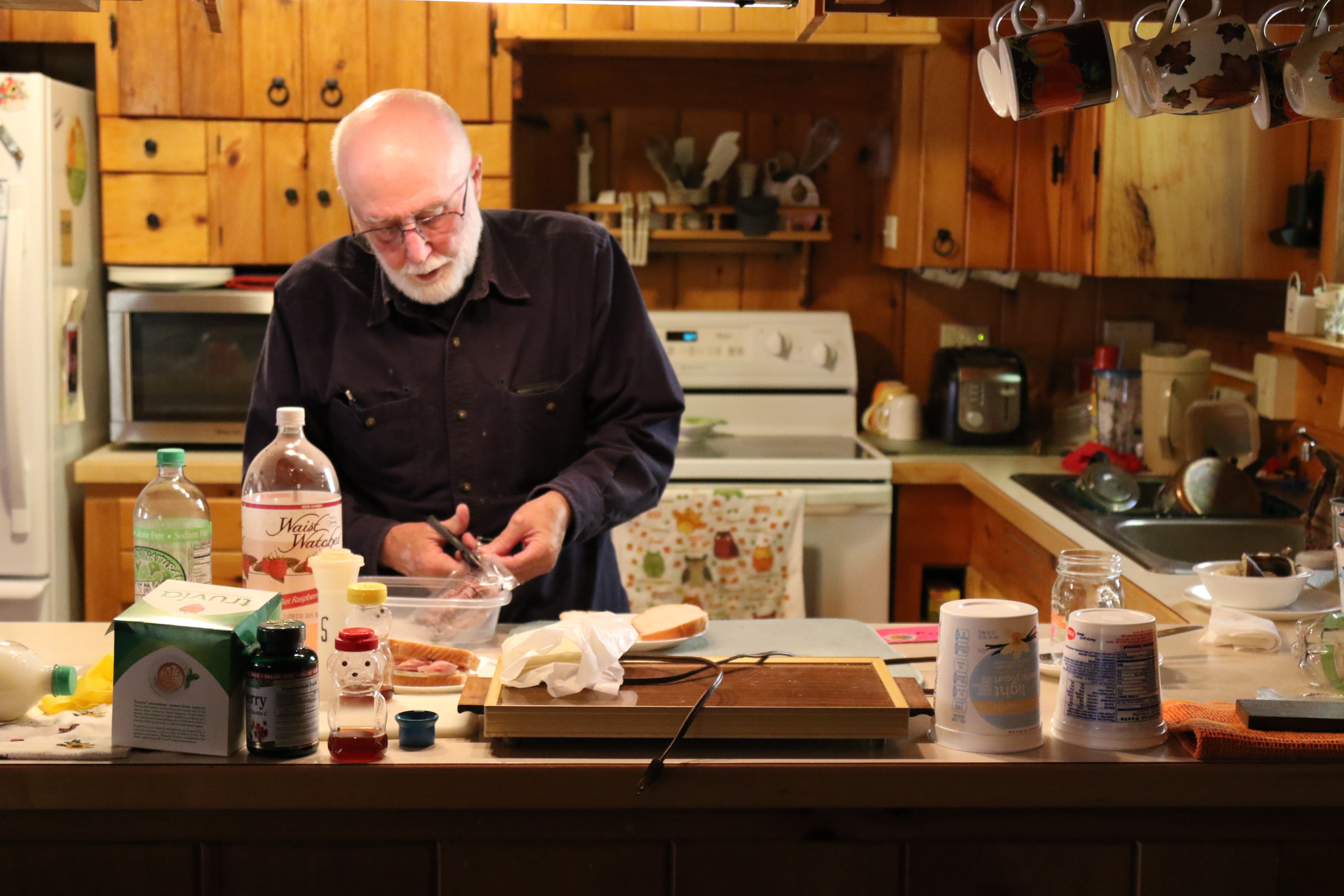 George prepares lunch for himself and Ann in his home in Mansfield, Connecticut. Since Ann's diagnosis, George has taken on nearly all of the household duties, including cooking. (Jackson Mitchell)