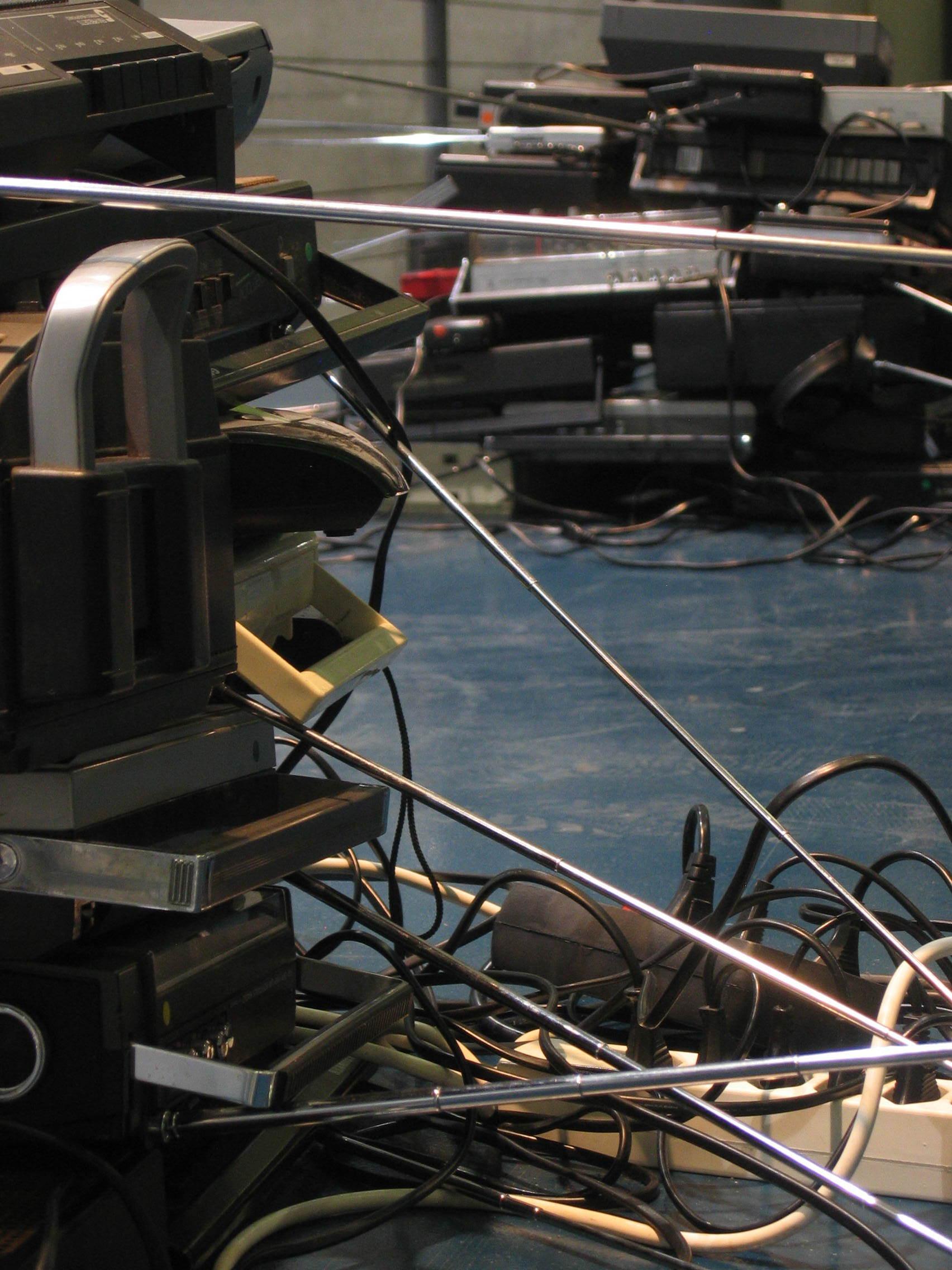 im laufe der ausstellungsdauer manifestiert sich zudem –ähnlich wie beim verbrennen des abfalls – ein prozess der vergänglichkeit. die radios weichen immer mehr von den zu beginn justierten rrequenzen ab und bringen sich durch fetzen benachbarter radiofrequenzen als eigenwilliges medium in die präzise komponierte installation ein.