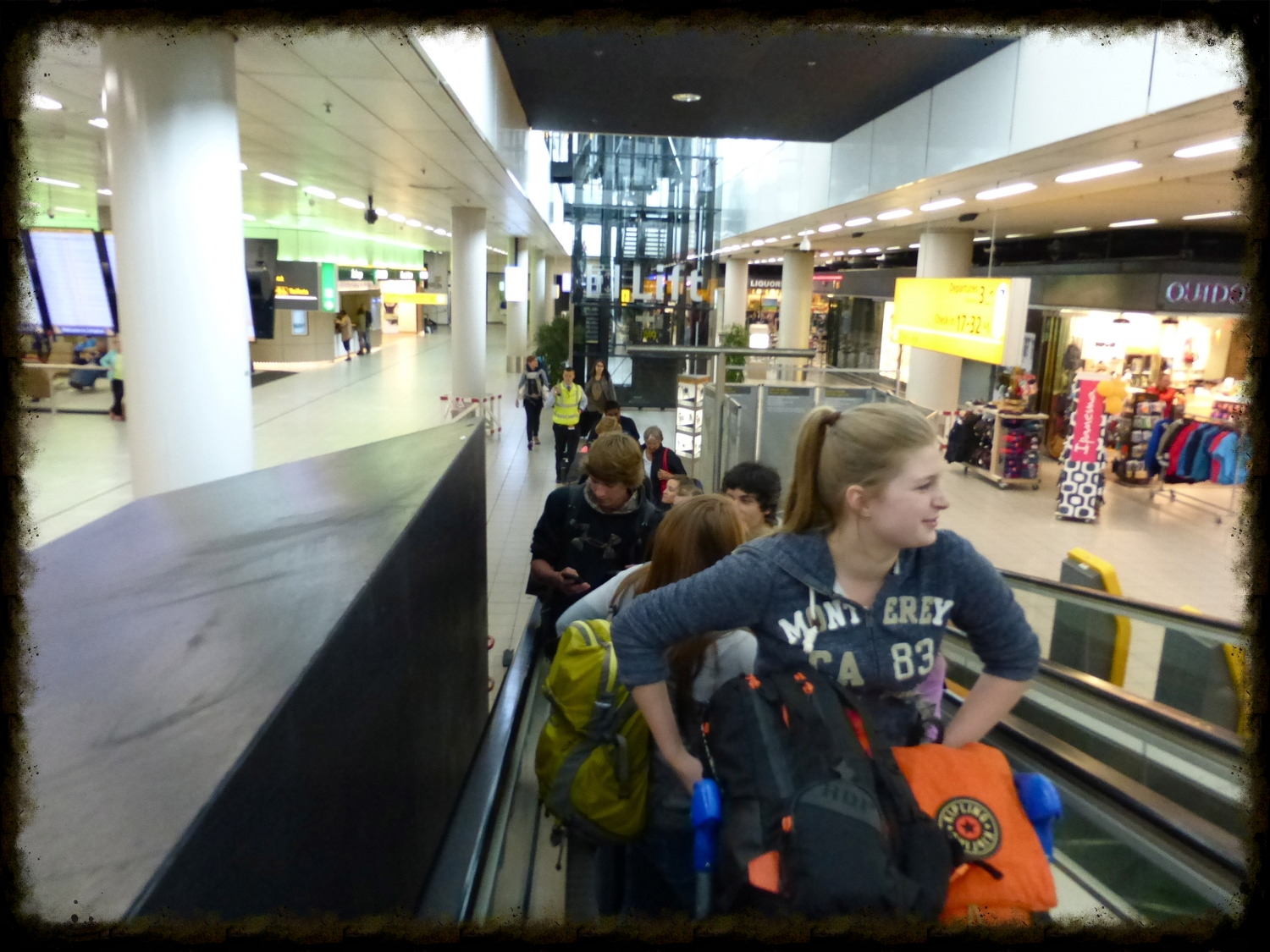 At Schiphol airport, ascending the escalator to check in!   photo courtesy of Chanthea de Jonge