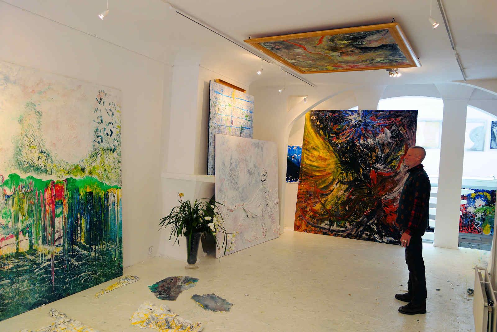 Harry van Gestel with one of his large paintings displayed on the ceiling