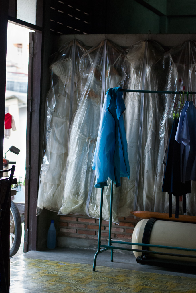 White wedding dresses hang in open doorway, Thasala