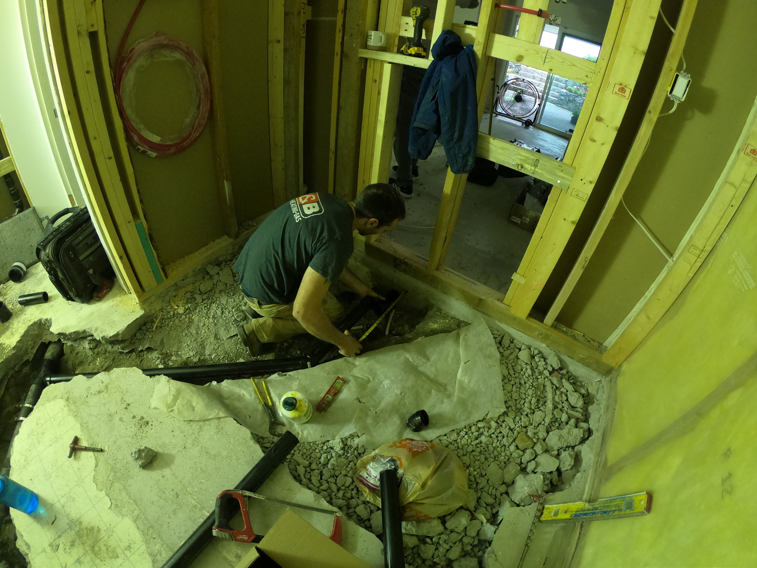 Plumber running the new shower drain catch to its new location for this North Vancouver Renovation