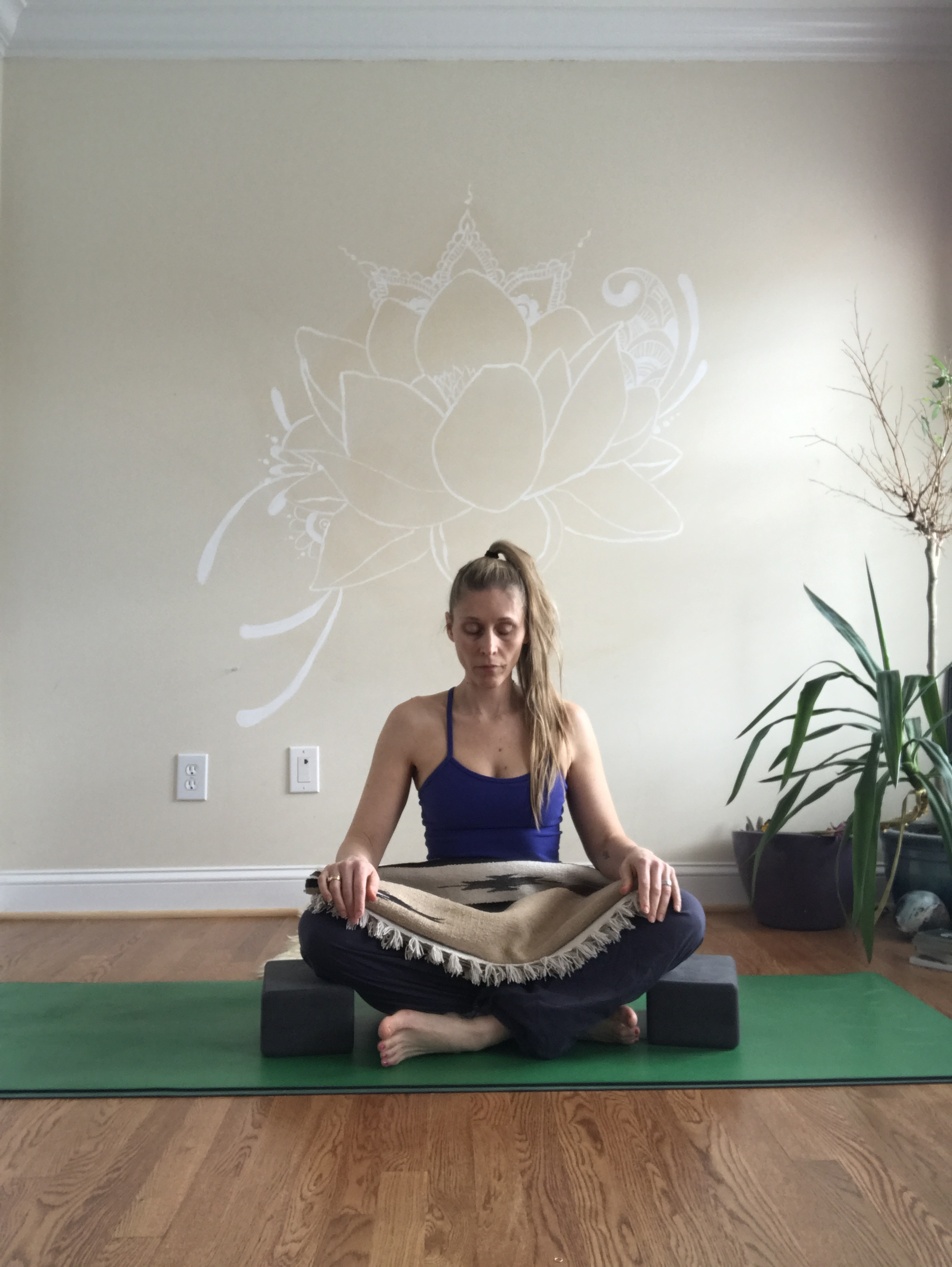Simple Cross Legged - Sit in a comfortable cross-legged position(or bring the soles of your feet together in front of you). Place a blanket over your lap and a block beneath each knee. You could take a moment to rub your feet or simply enjoy a few quiet breaths here.