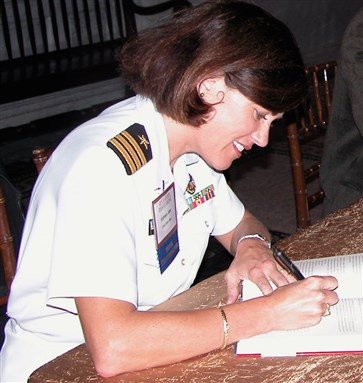 [Navy Reserve Cmdr. Kathleen Toomey Jabs autographs a copy of Operation Homecoming; image from Defense.gov]