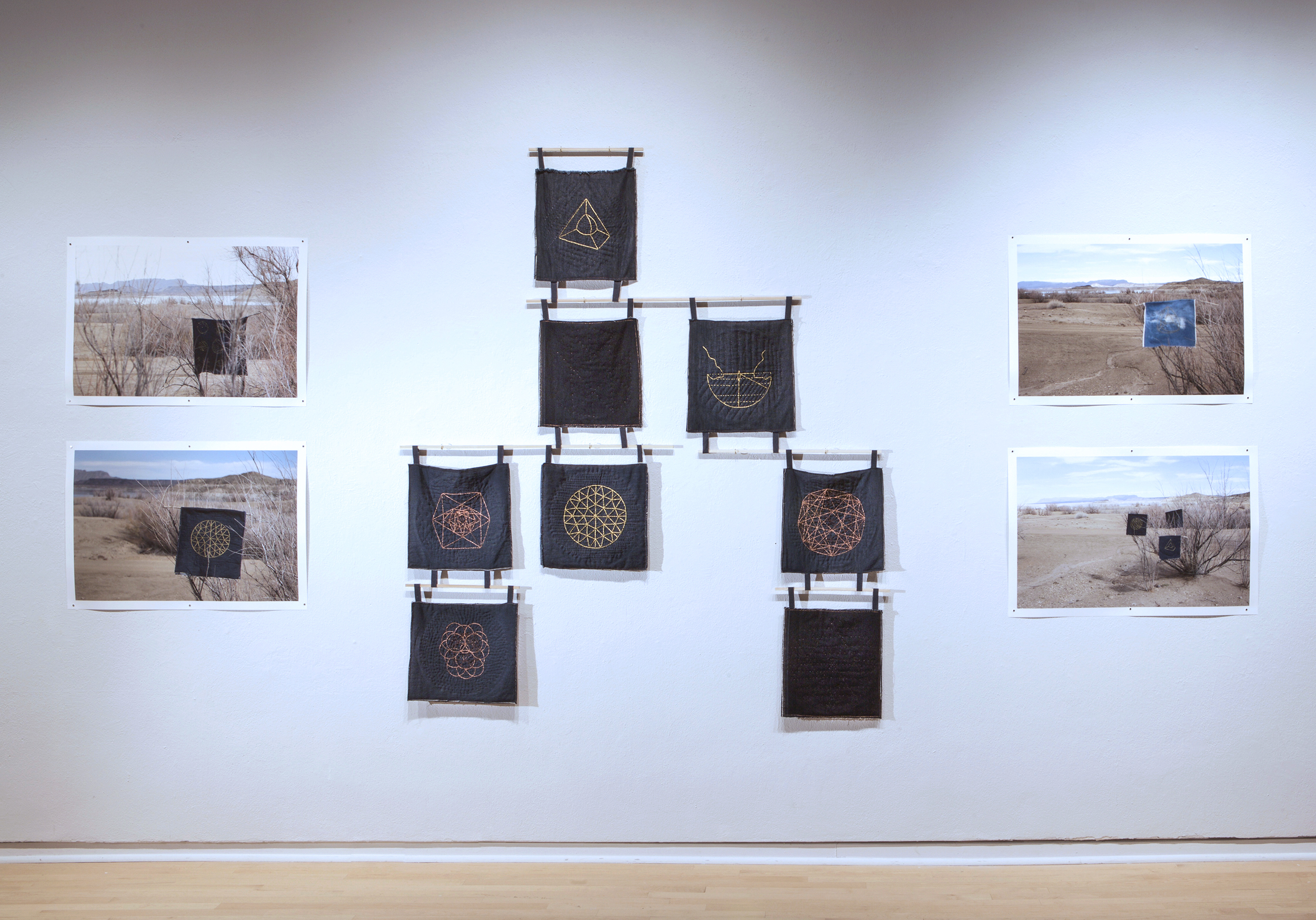 "Installation View: (center)  Whole Earth Samplers , 2017, Denim, metallic embroidery thread, wood, dimensions variable, each sampler: 10"" x 10"" (left and right)  Whole Earth Samplers at Elephant Butte, NM I-IV , 2017, Inkjet prints, edition of 5, 20"" x 30"""