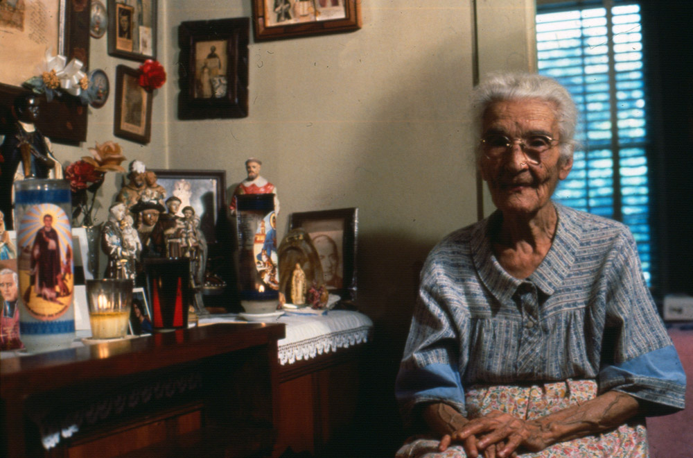 """Photo by Kay Turner, Austin, TX 1979 Soledad """"Chole"""" Pescina at home with her personal altar."""