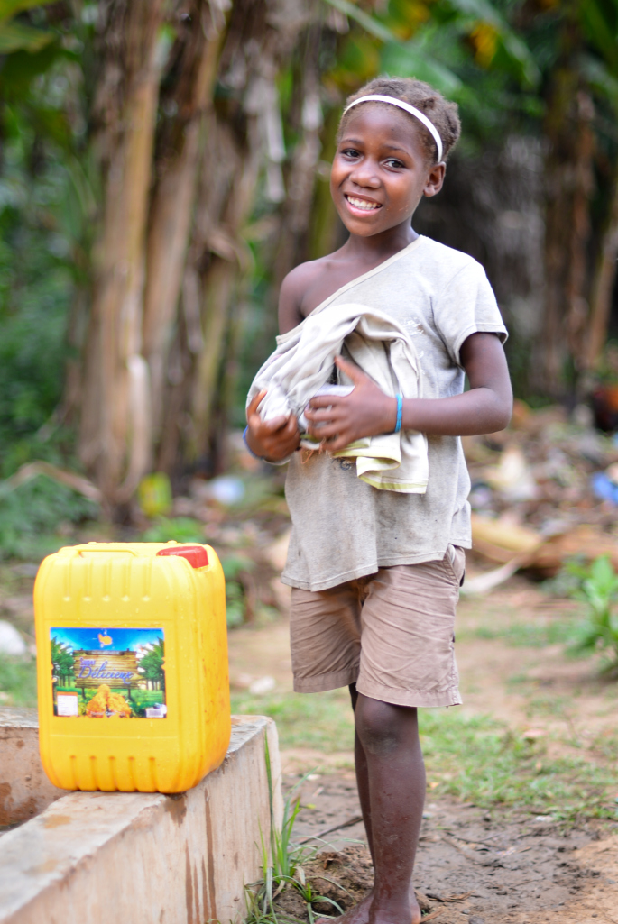 Bringing well water home to her family wearing a smile.