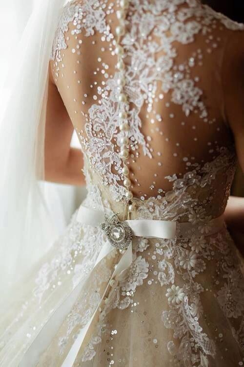 Sheer wedding dress embellished with pearls and rhinestone crystals.