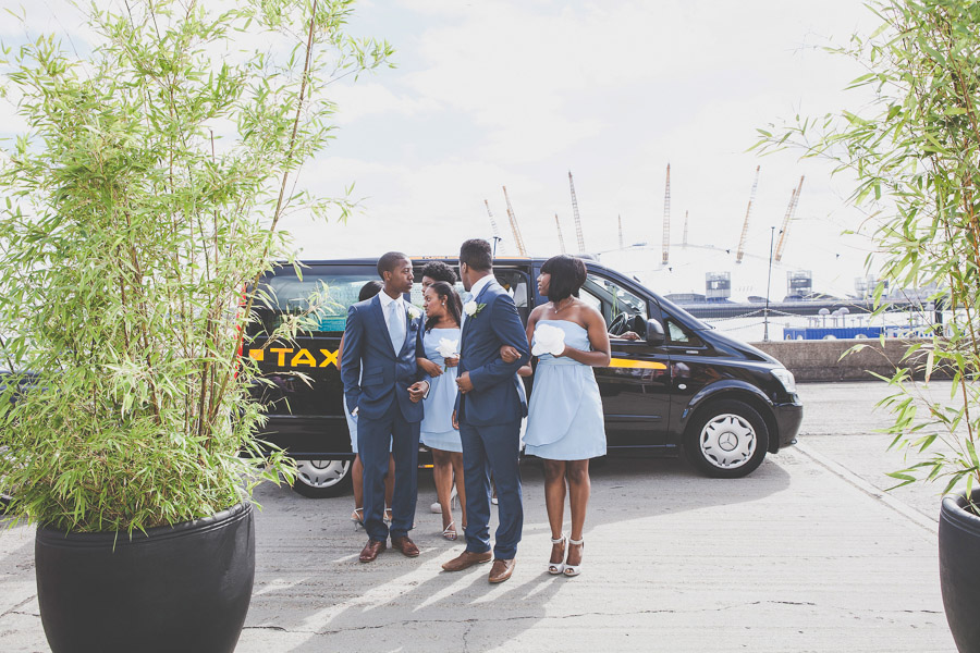 Ushers and bridesmaids arrive in a London taxi