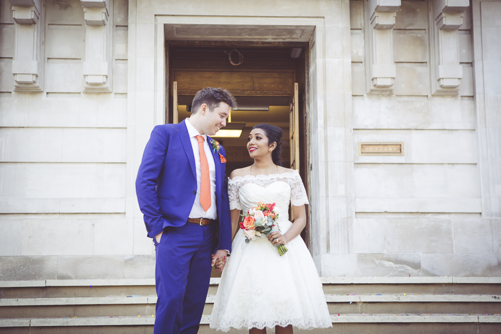 Bride and groom on steps of Hackney Town Hall