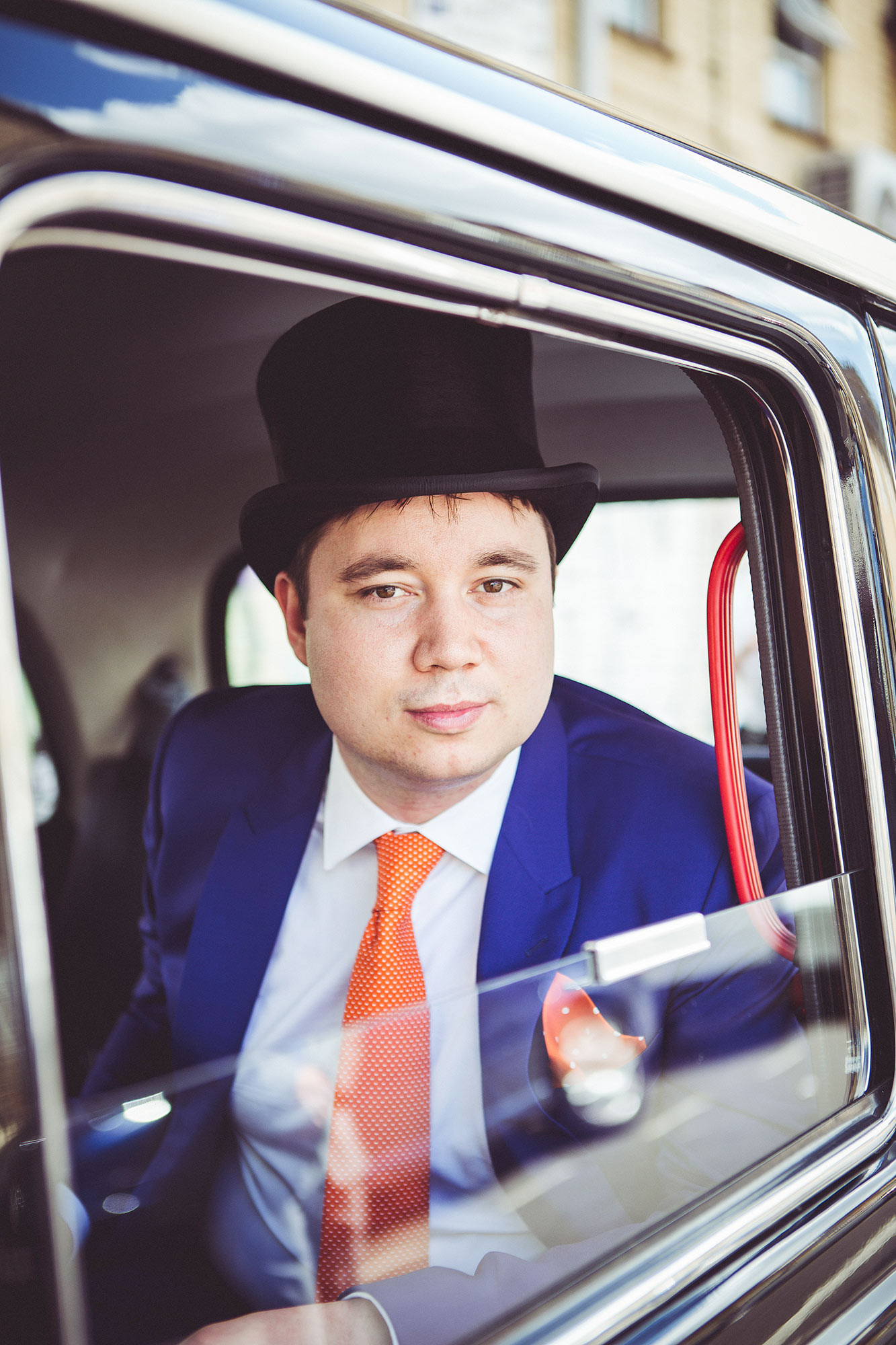Groom in london taxi wearing a top hat