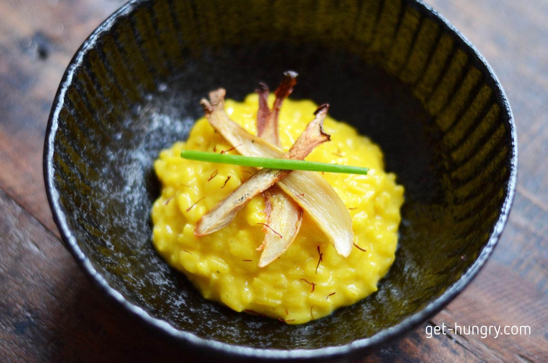 """Der  Legende  nach erfunden wurde das Mailänder Risotto bereits im 16. Jahrhundert. Ob der gelbfärbende Safran aber durch Zufall in den Reis kam oder man """"vergoldetes Essen"""" der Reichen imitieren wollte, bleibt für immer unklar."""