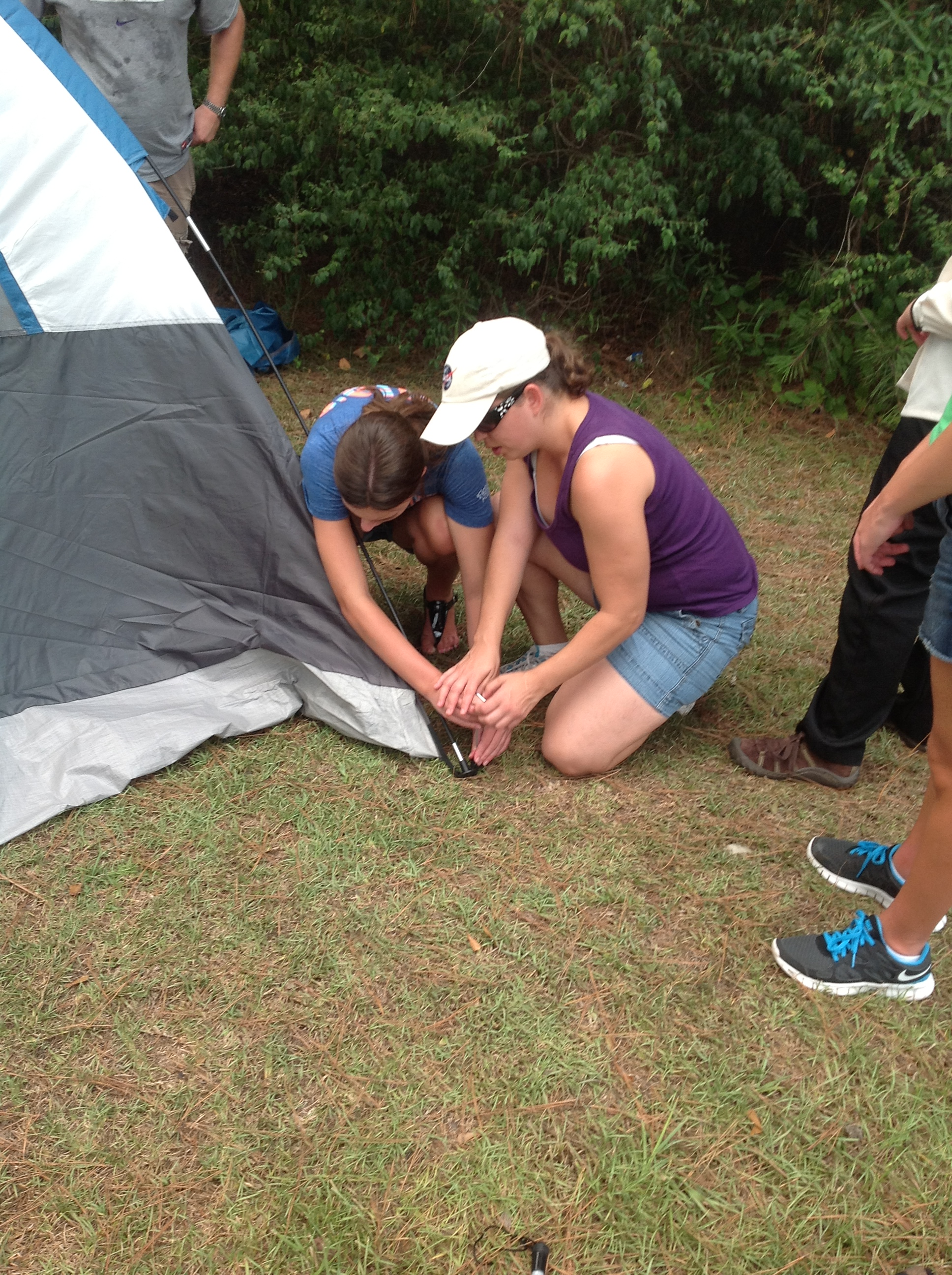 Counselor and student drop the hammer on a tent stake.