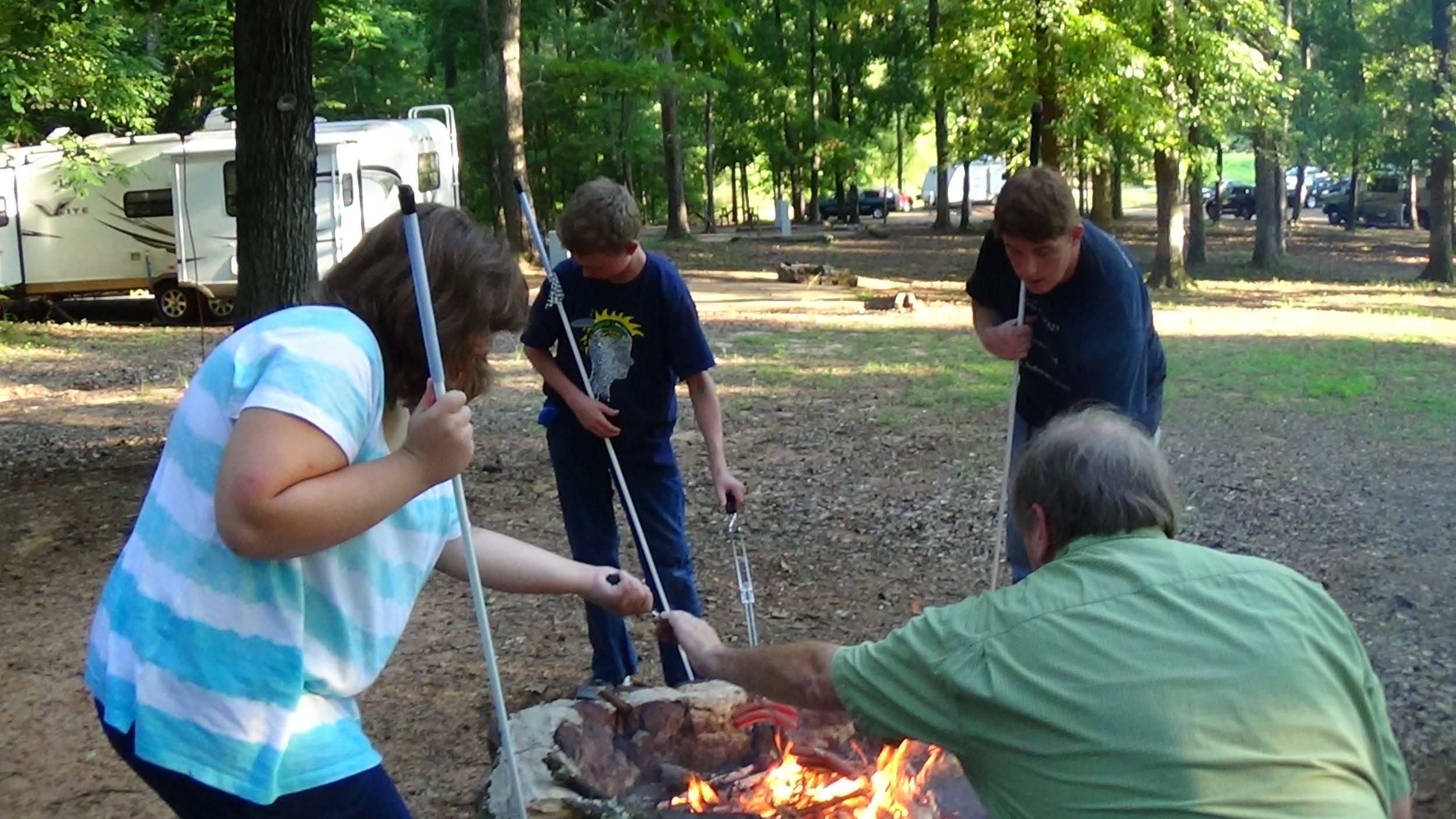 2013 STEP students roast hot dogs over a fire pit.