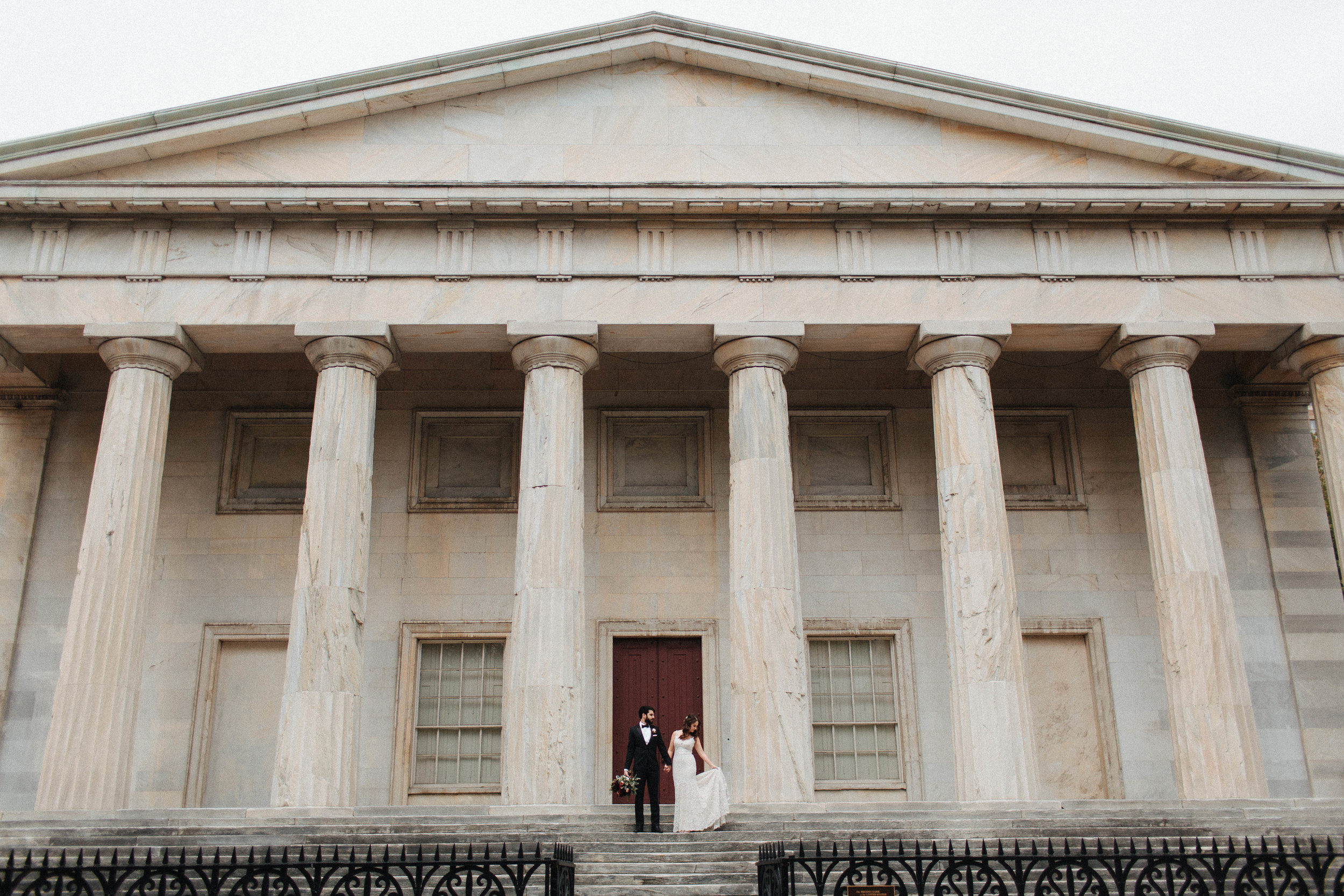 bride and groom standing in front of historic Philadelphia building
