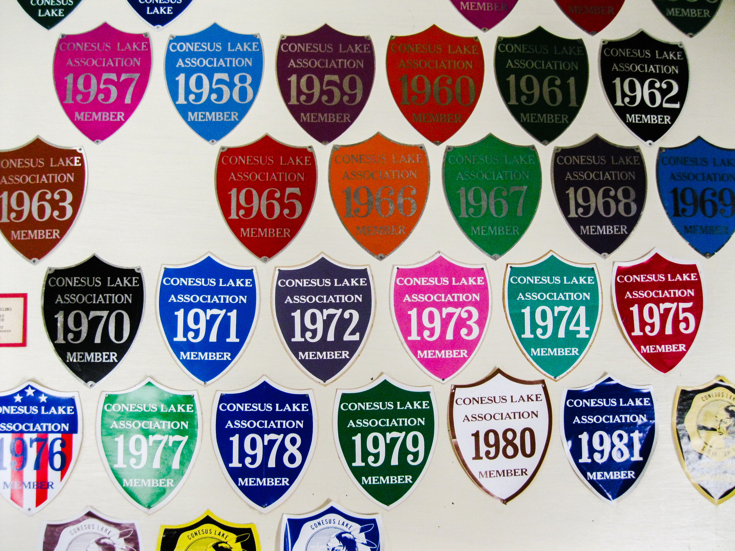 """These decals from 1950-1985 honor the history of the Conesus Lake Association, founded in 1932 as the Conesus Lake Cottagers' Association.   Their aim is to """"promote the health, safety, and welfare of the residents, both permanent and temporary, of the area community known as Conesus Lake, Livingston County, New York. The Association encourages all residents to proudly display Conesus decals """"to show you care for the future of our Lake.""""   Currently, Conesus Lake serves as the water supply for almost one fourth, or over 18,000 residents of Livingston County."""