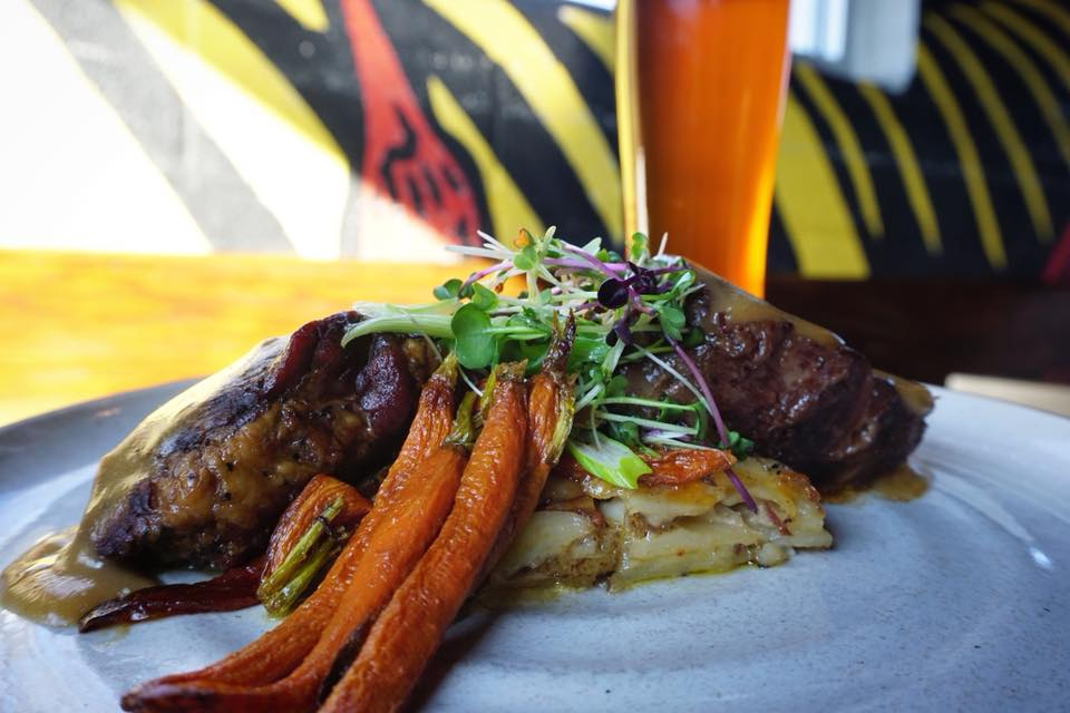 'Braised Short Rib'. Drizzled with bourbon gravy, our braised short rib sits on a bed of housemade scallop potatoes with roasted carrots.