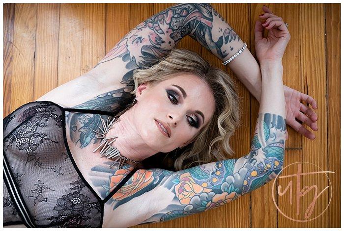 boudoir photography denver floor pose face tattoo sleeves.jpg