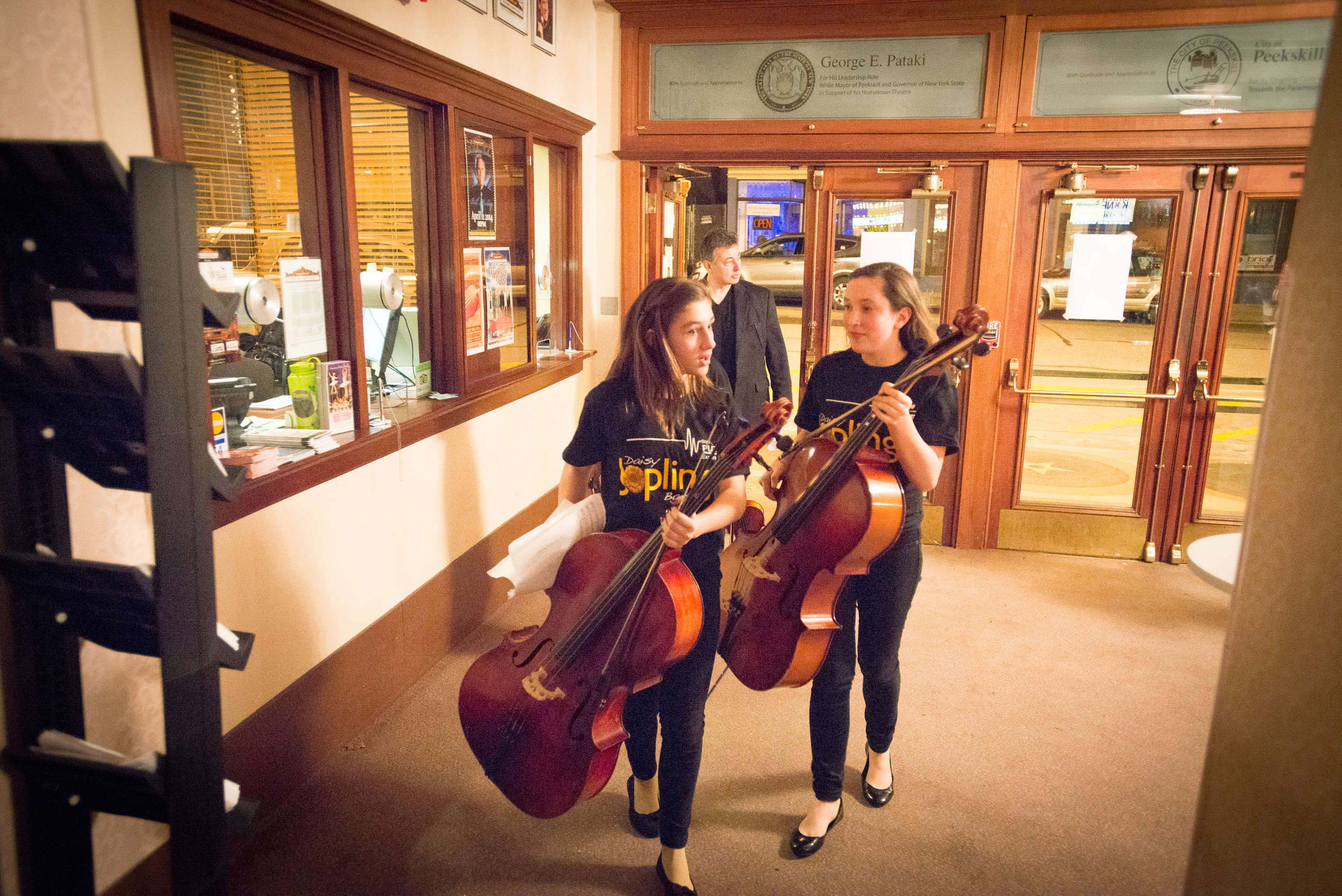 2 cellists as they walk around the back of the Paramount Hudson Valley through the lobby back to their seats after performing on stage