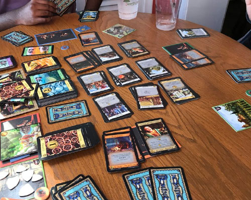 Playing a strategic card game, Dominion, to work on executive functioning, socialization, and fine-motor skills.